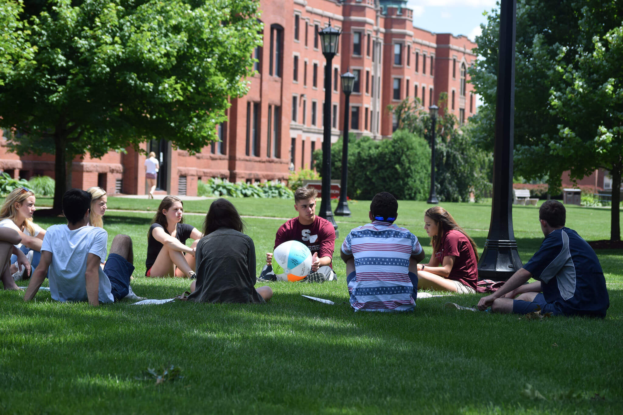 Students sitting in a circle on Naismith Green.