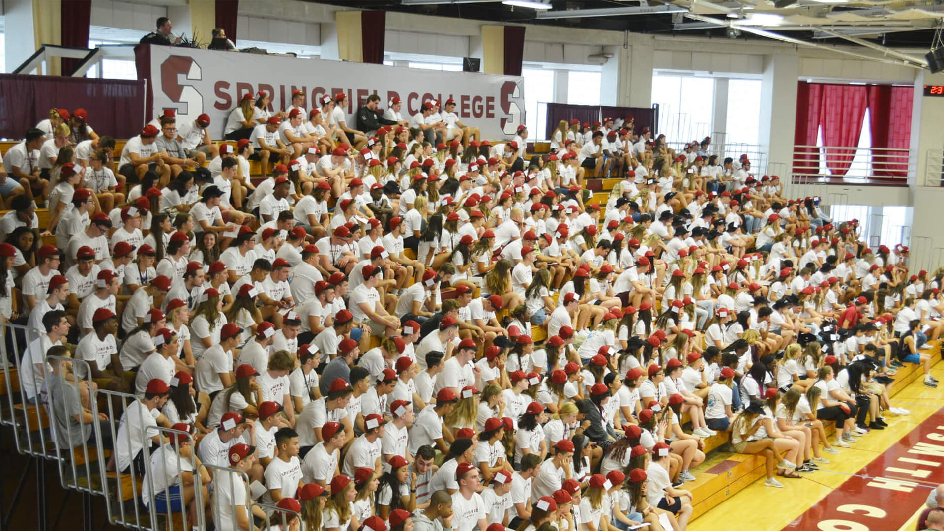 New students sit in the bleachers wearing beanies for their convocation.