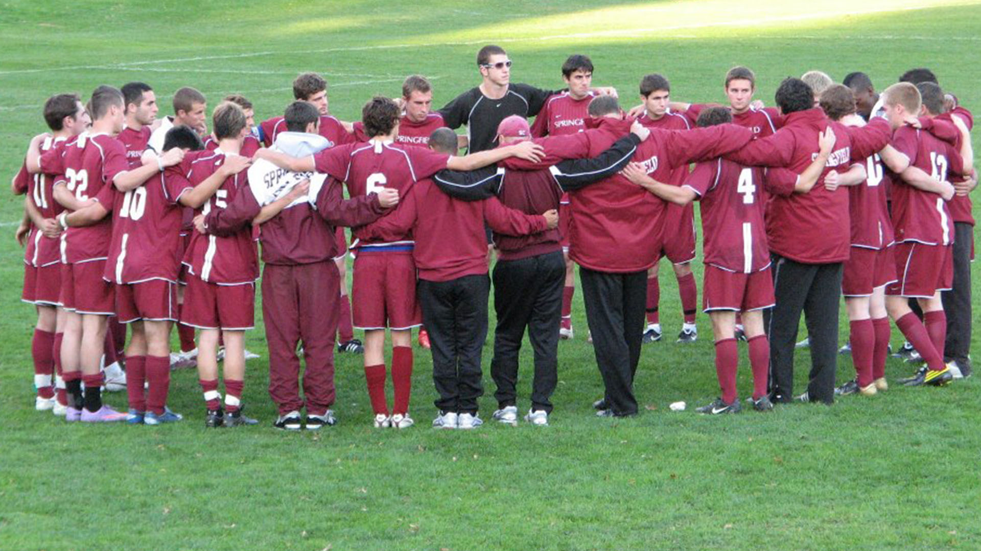 Soccer team huddled on the field.