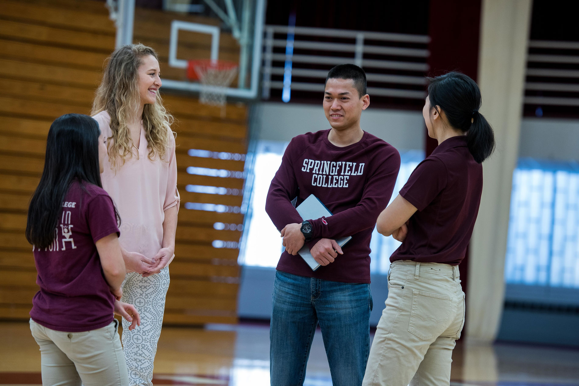 Students in the School of Physical Education, Performance and Sport Leadership stand in the basketball court at Springfield College while having a conversation.