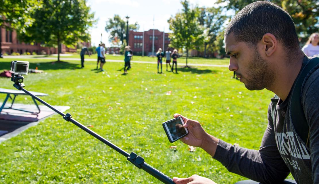 A student looks at his phone as he works on a project on the campus green.