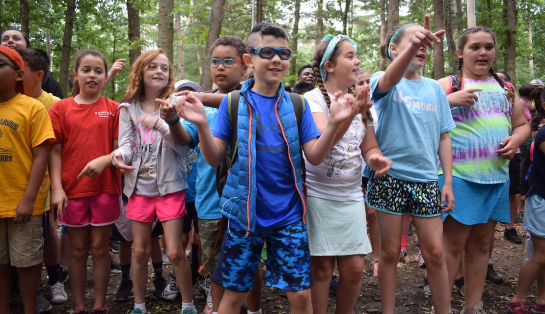 A group of campers cheer and clap at Camp Massasoit.