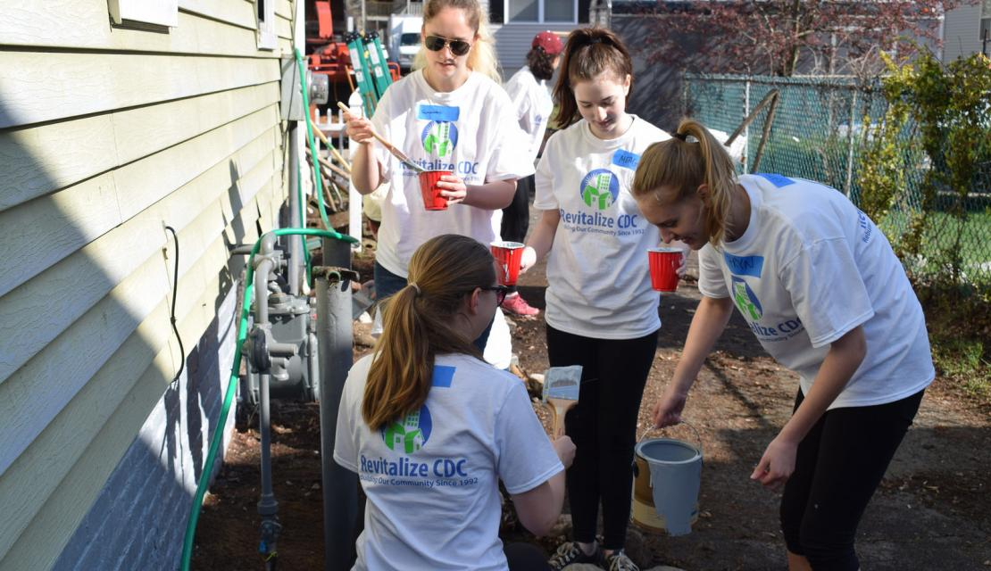 Students help fix up a downtown home as part of revitalization.