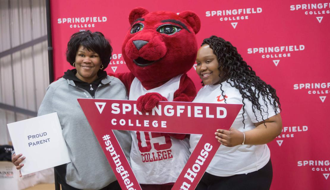 An incoming student and her mother pose with the mascot at Accepted Student Open House.