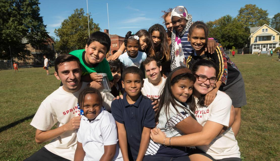 Springfield College students pose on the playground with the students they are volunteering with.