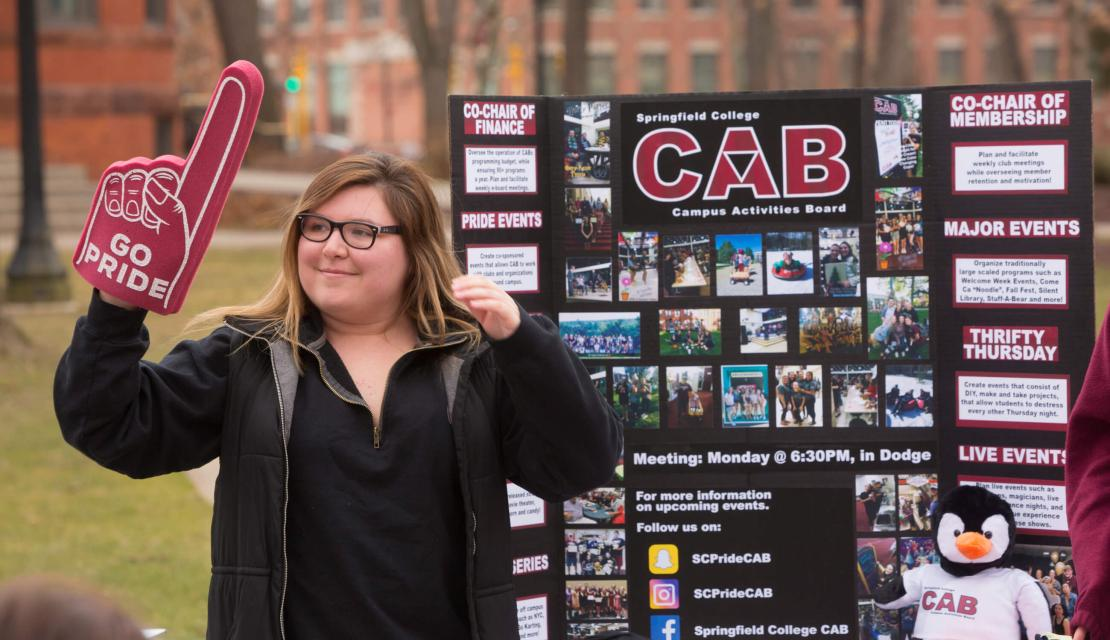 A student stands by a poster promoting an on campus club.