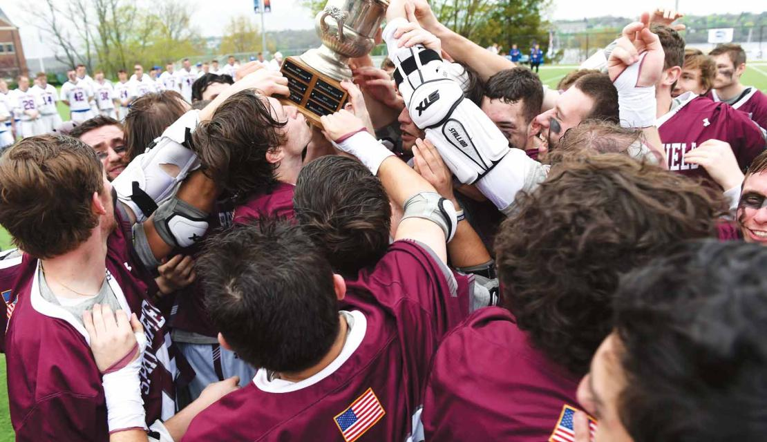 Springfield College men's lacrosse team celebrates NEWMAC championship with with trophy