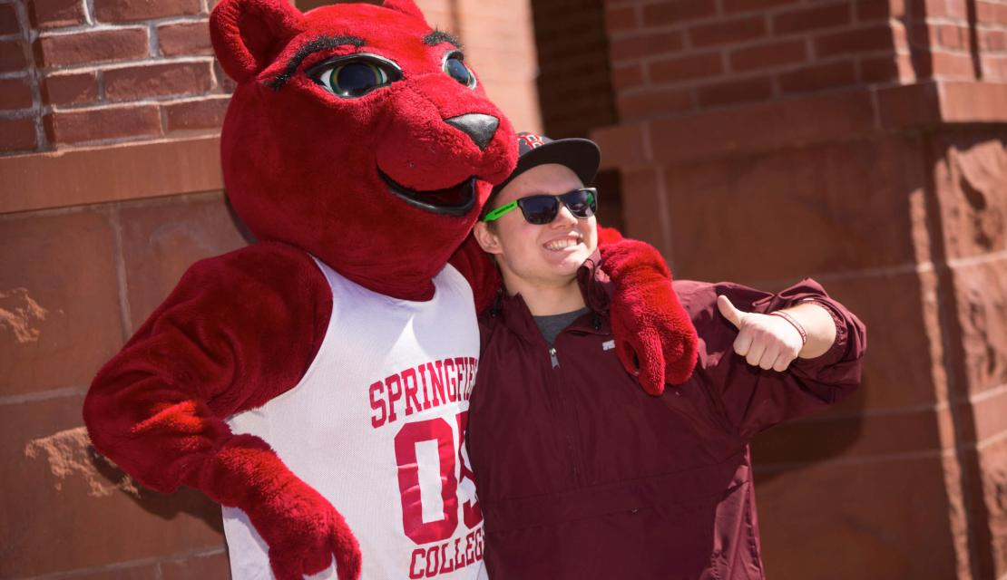 A student poses with the mascot