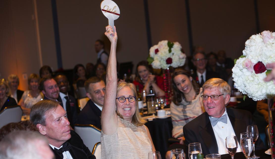 A woman holds up her auction paddle at Gala