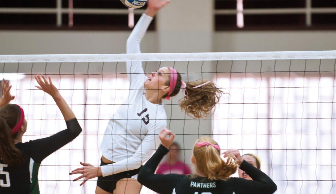 Mary Consol of Springfield College Volleyball spikes a volleyball over the net during a game