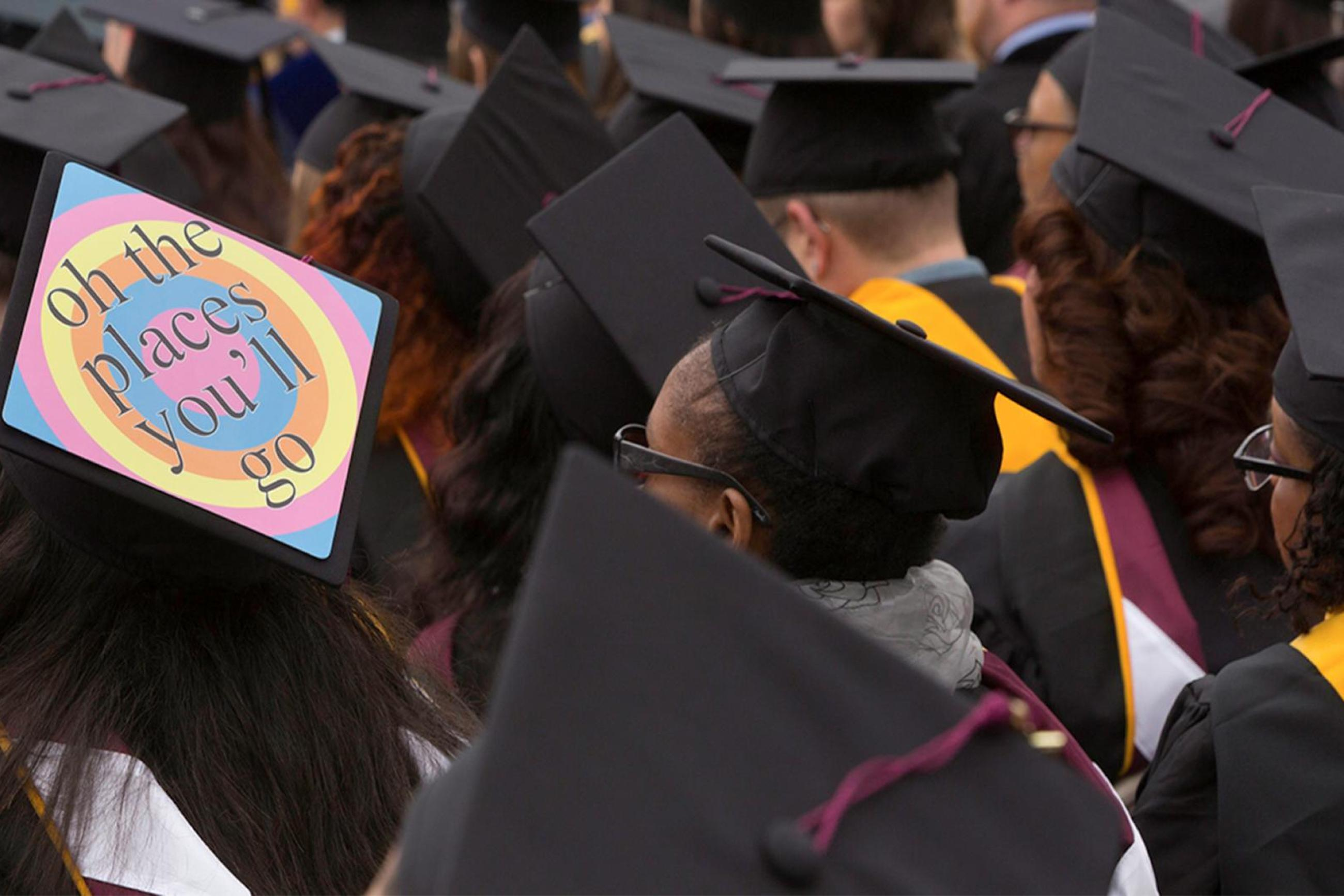"A student sits in the crowd at commencement with a mortar board that says ""Oh the places you'll go"""