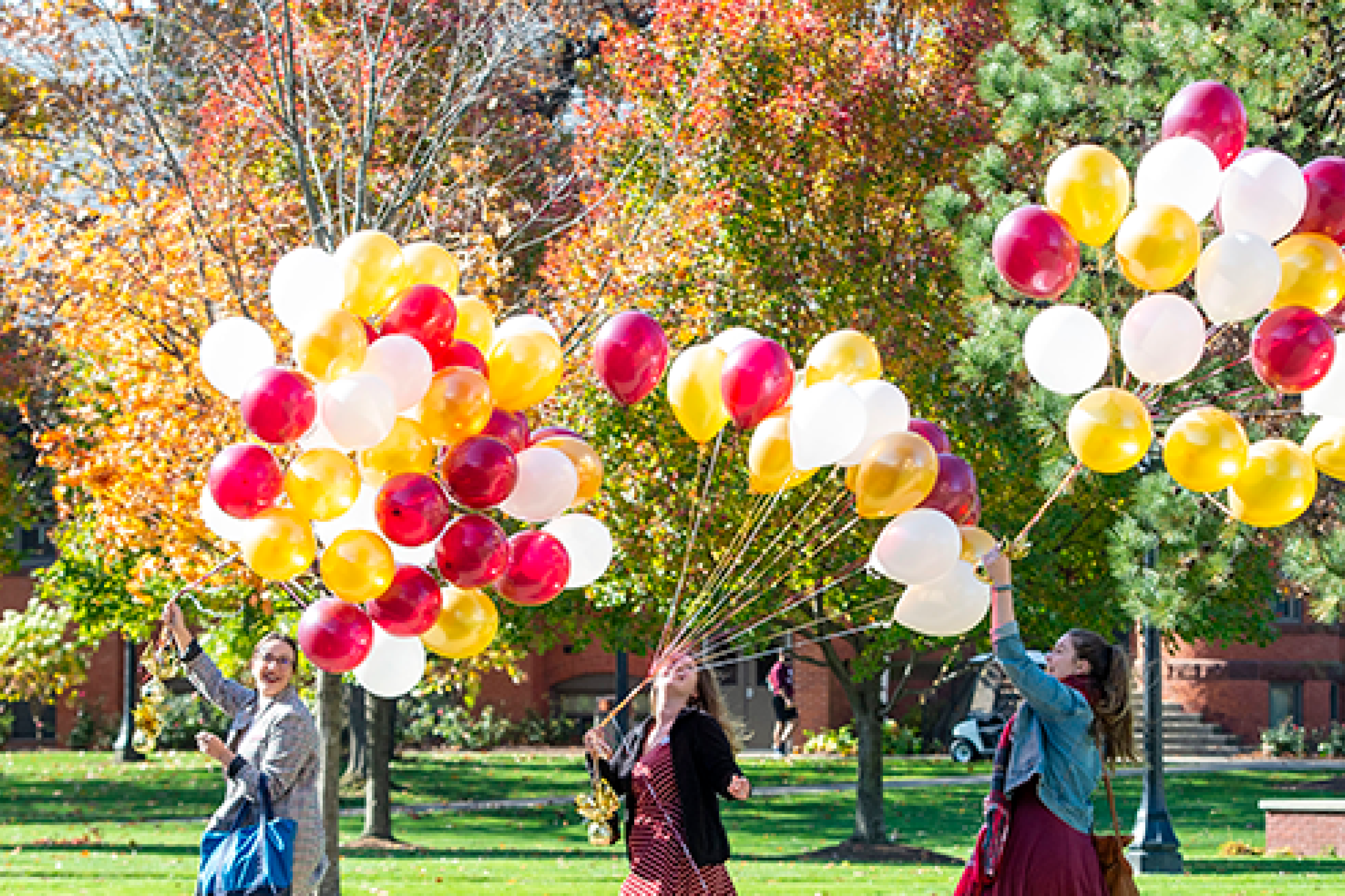 walking with balloons on campus