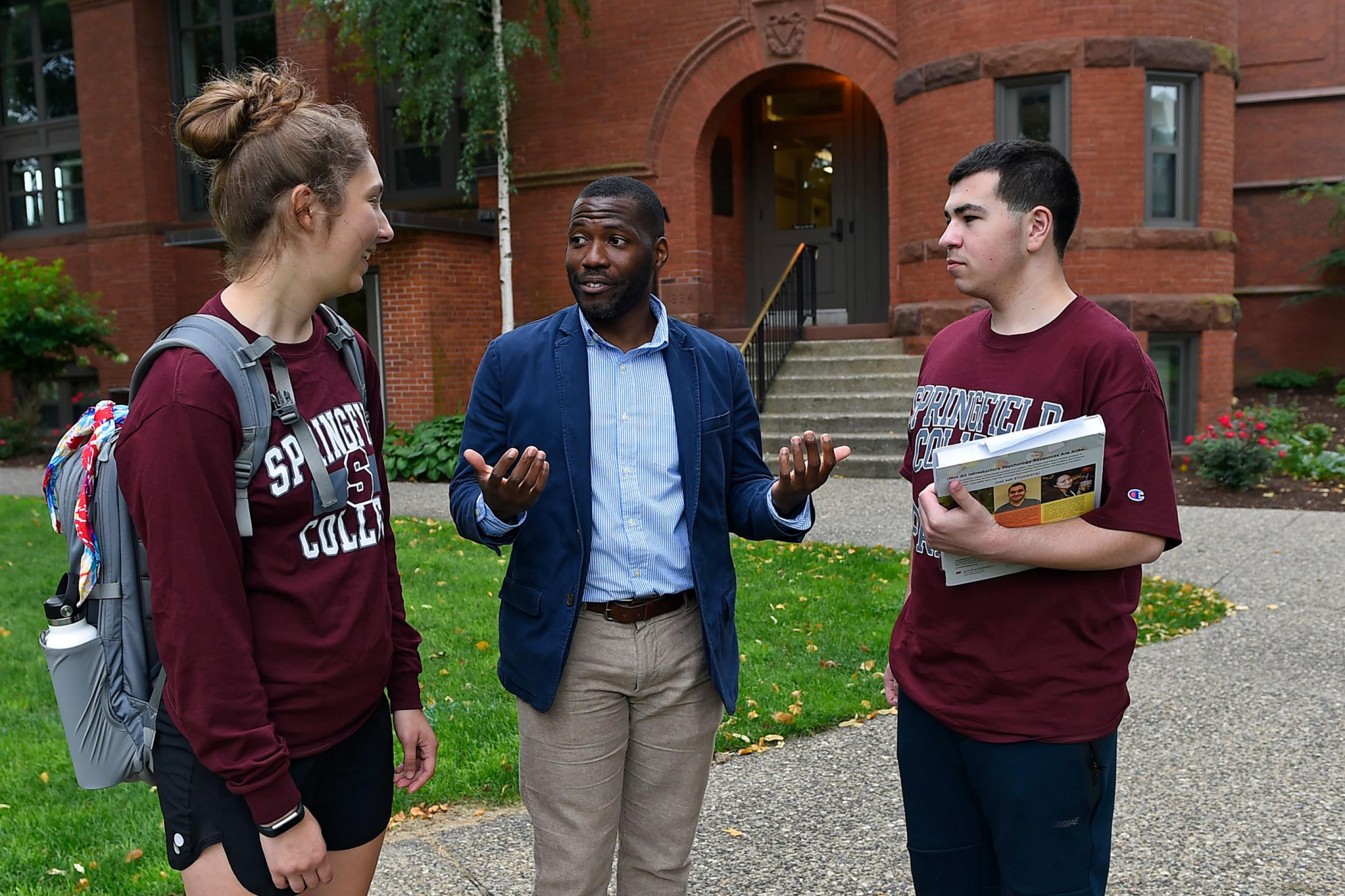 Professor Korey Boyd speaks with two Springfield College students