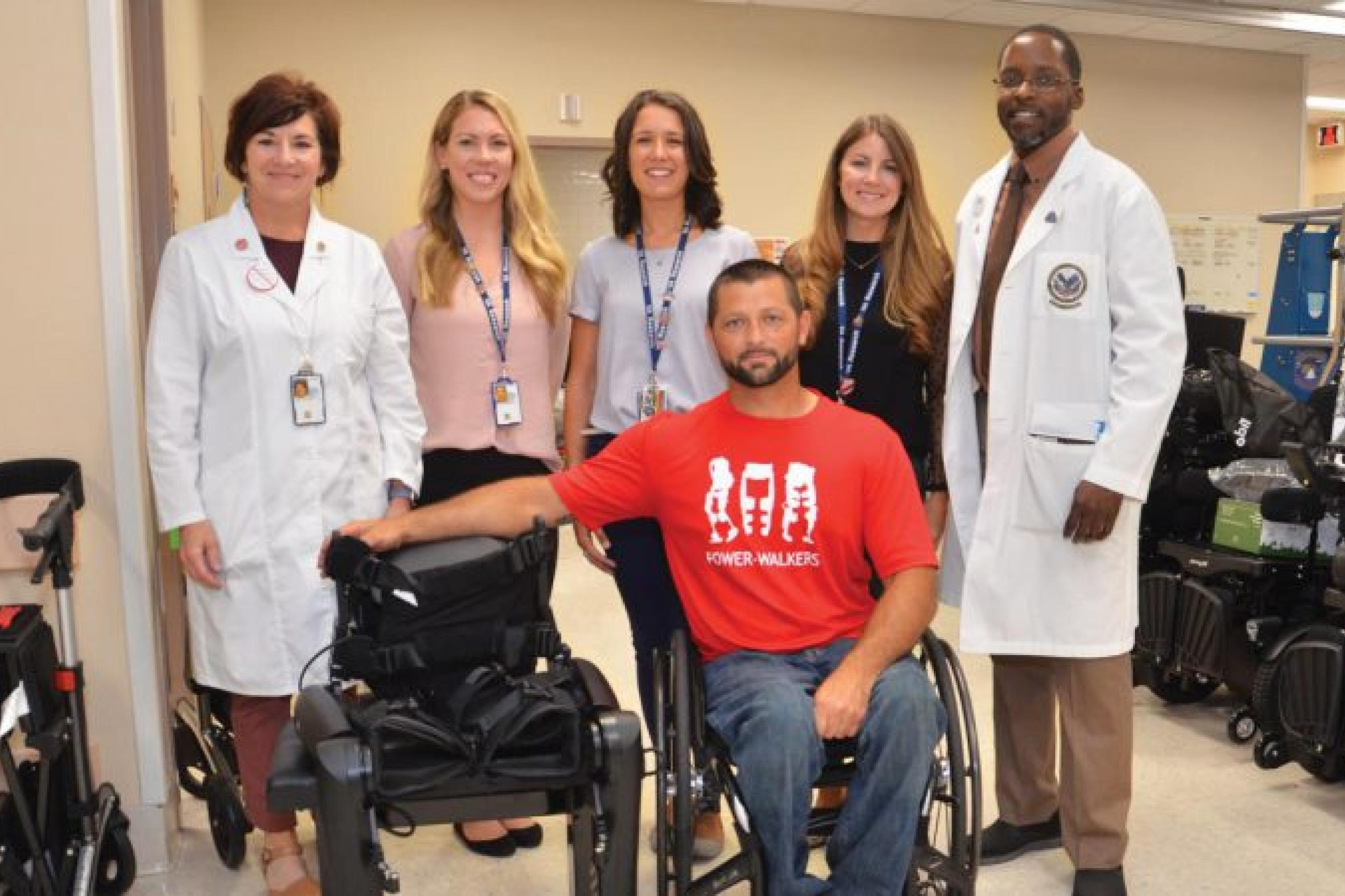 Veteran Tim Conner, seated, with his new exoskeleton and the team that helped make it possible