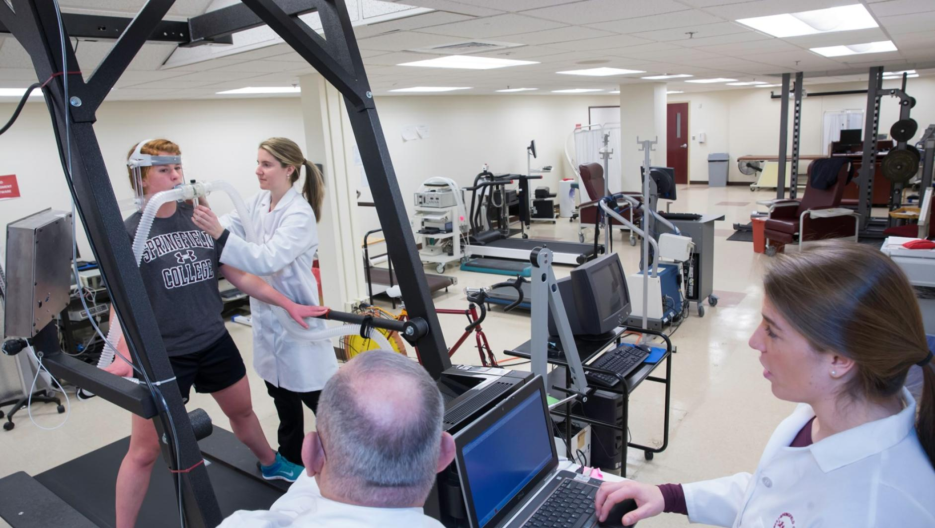 Student and faculty adjust the computer tracking system as a participant runs on the treadmill.