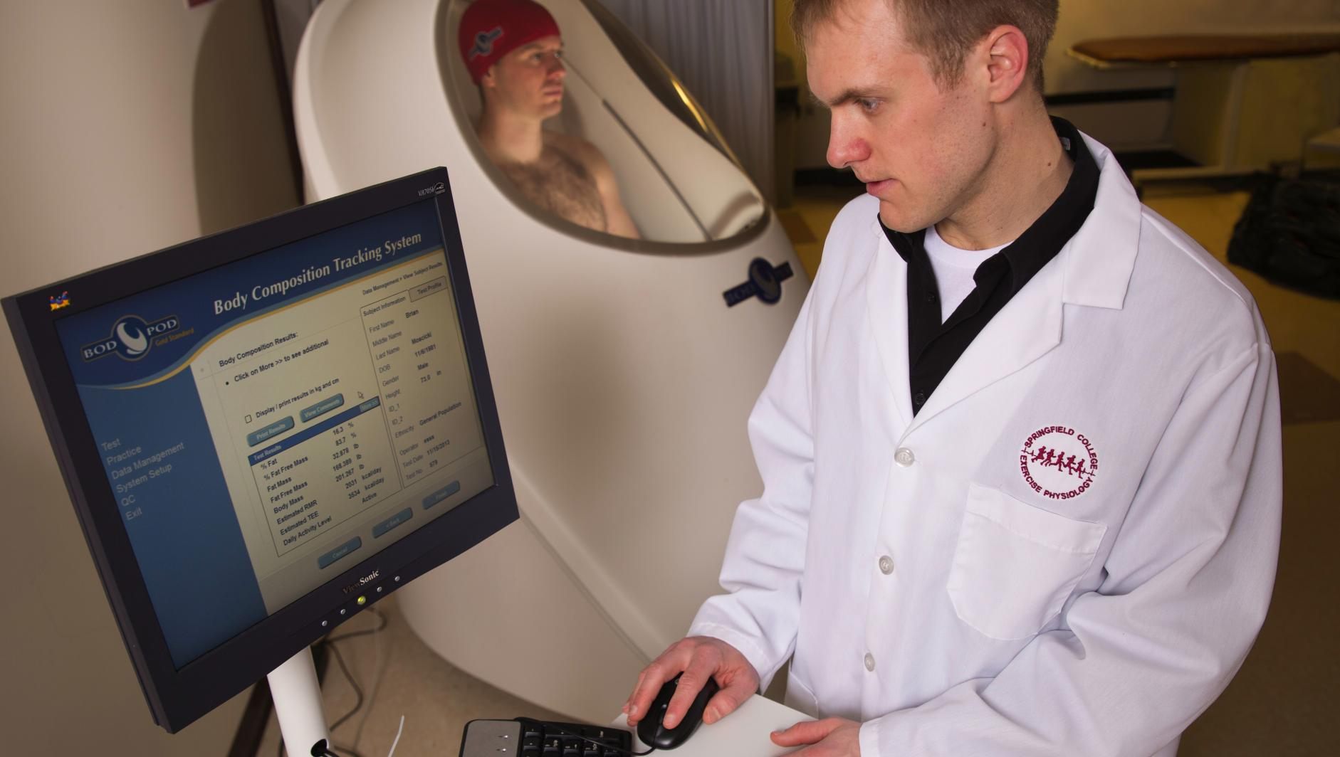 A student conducts testing on another student who is inside a BodPod in the human performance lab.