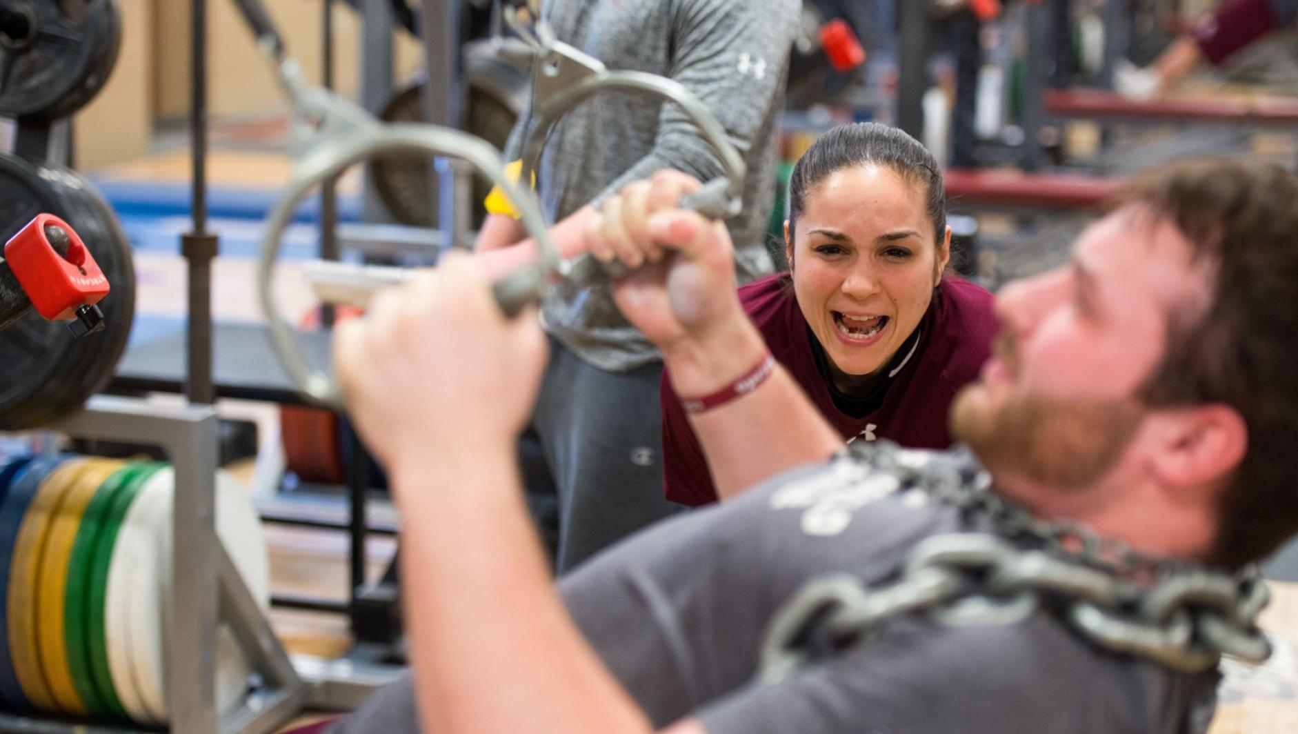 A student strength and conditioning coach yells words of encouragement as a student works out his arms.