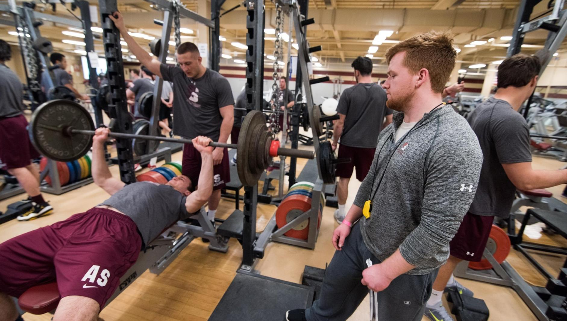 A student strength and conditioning coach looks on as his client does a chest press.