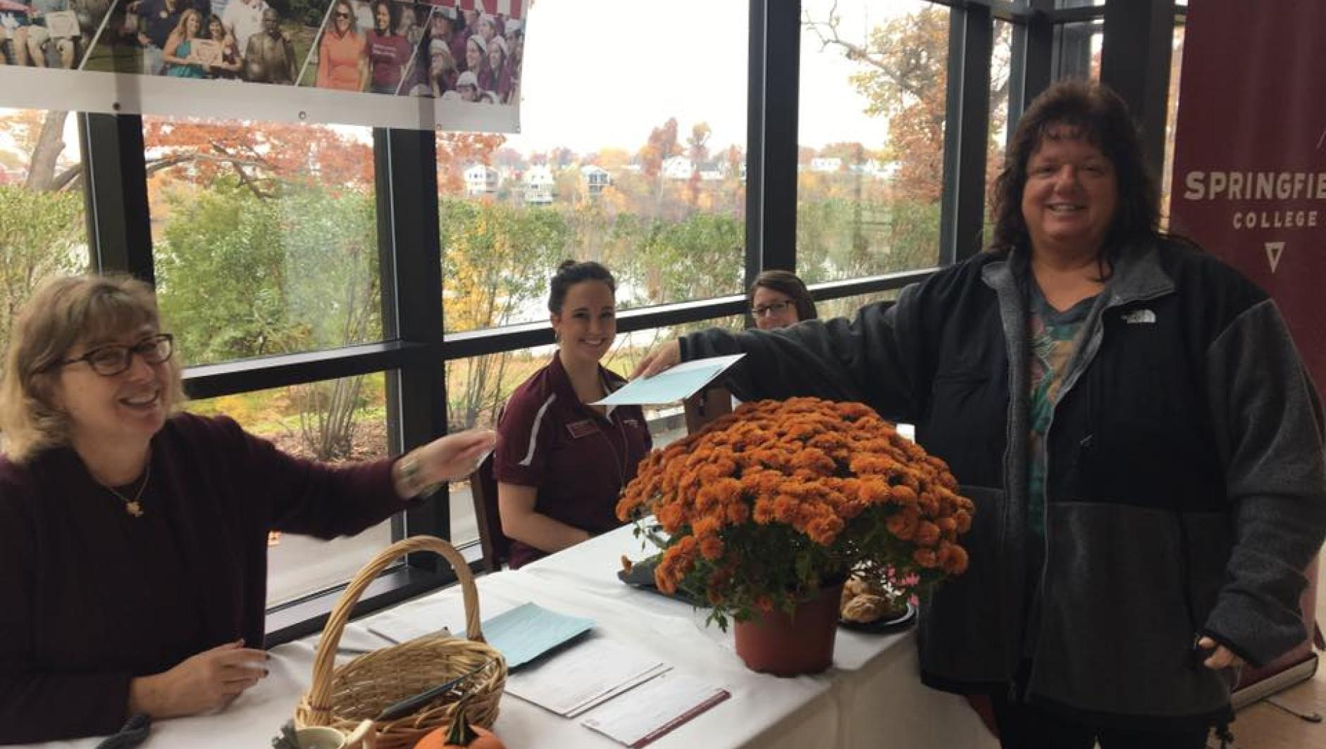 A Springfield College staff member makes a suggestion at the referral table during the day of recruitment.