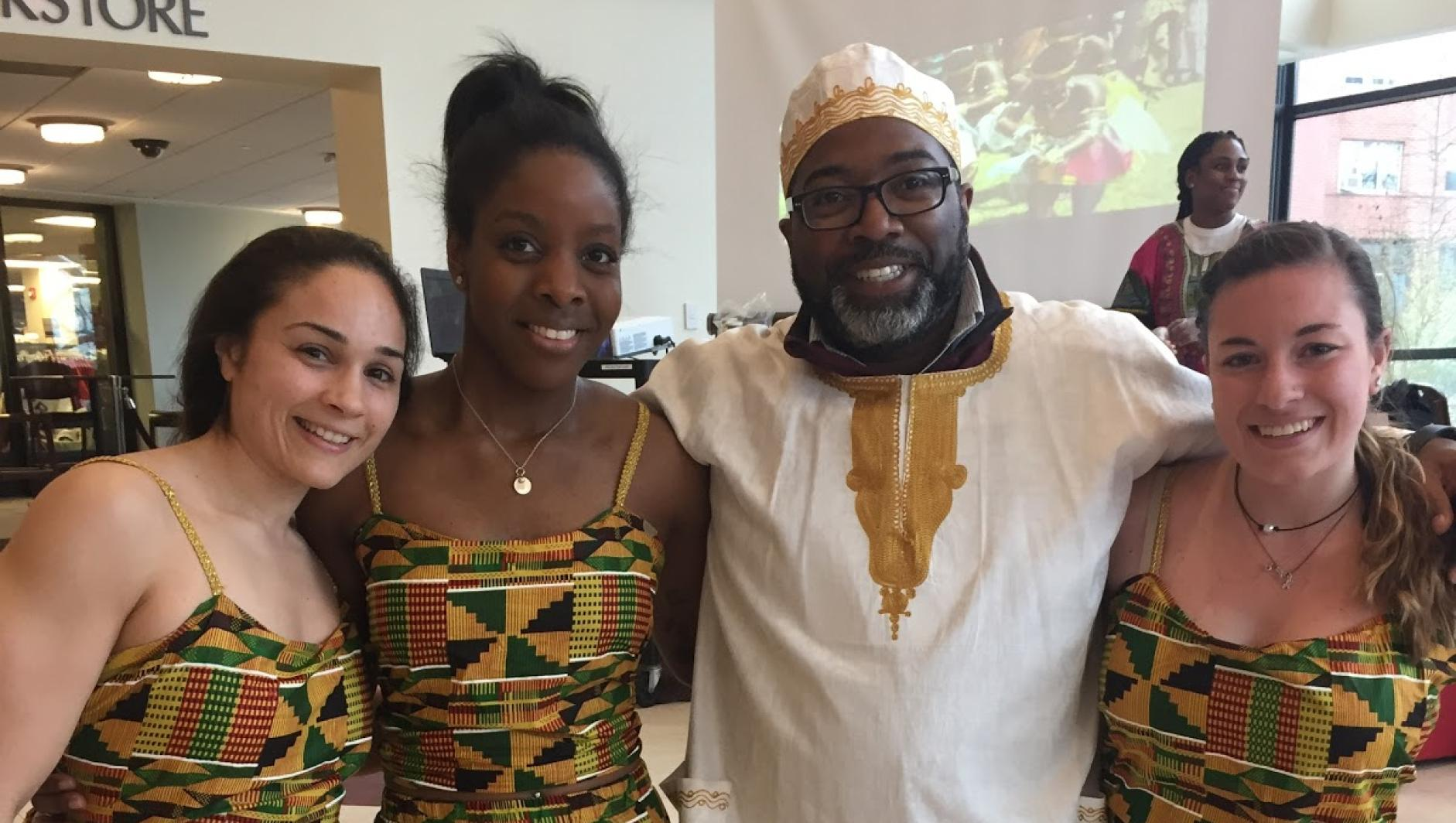 Calvin Hill poses with female students in traditional dress during African Cultural Day
