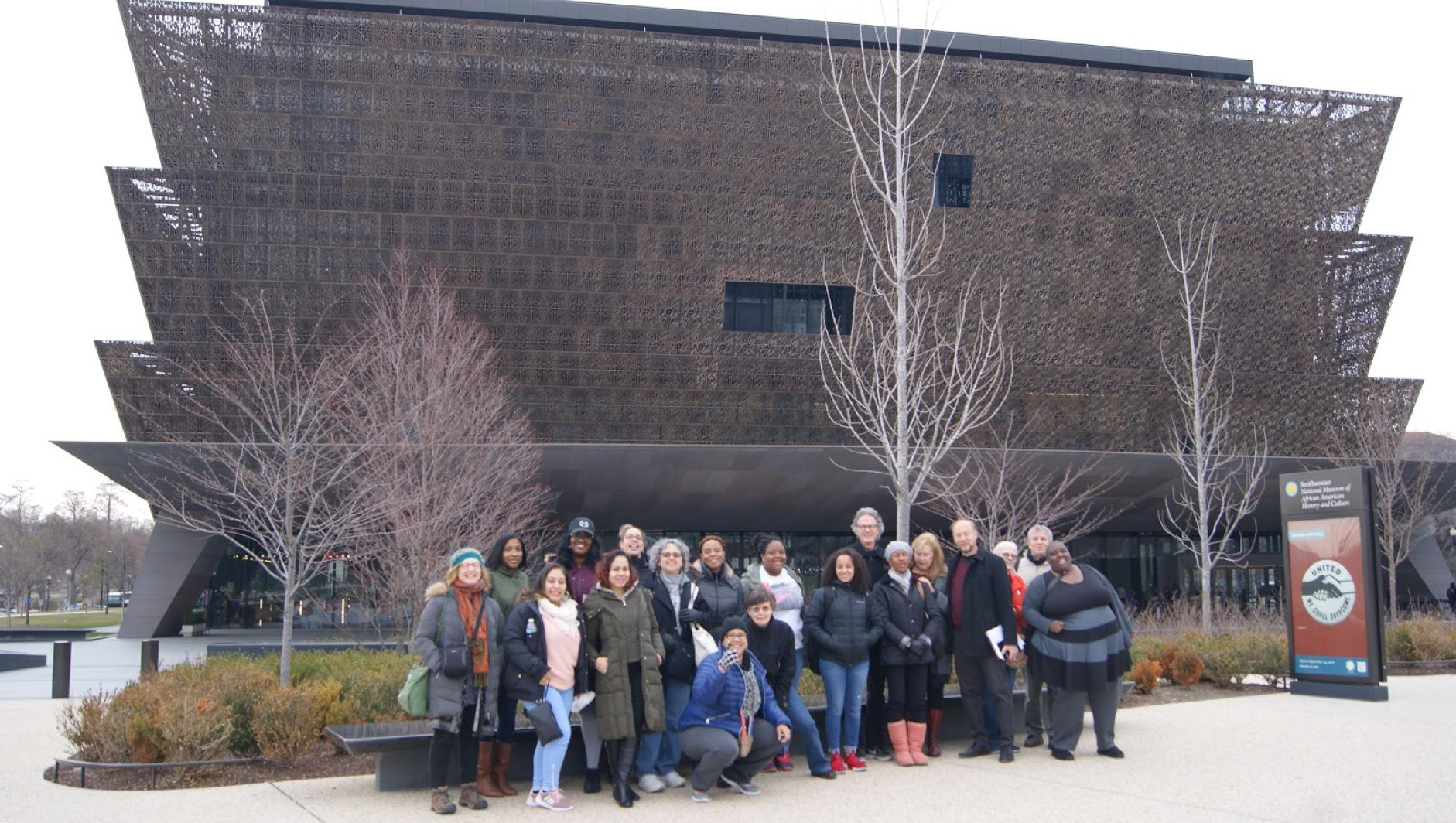 A group of Springfield College students pose outside of the Smithsonian National Museum of African American History and Culture