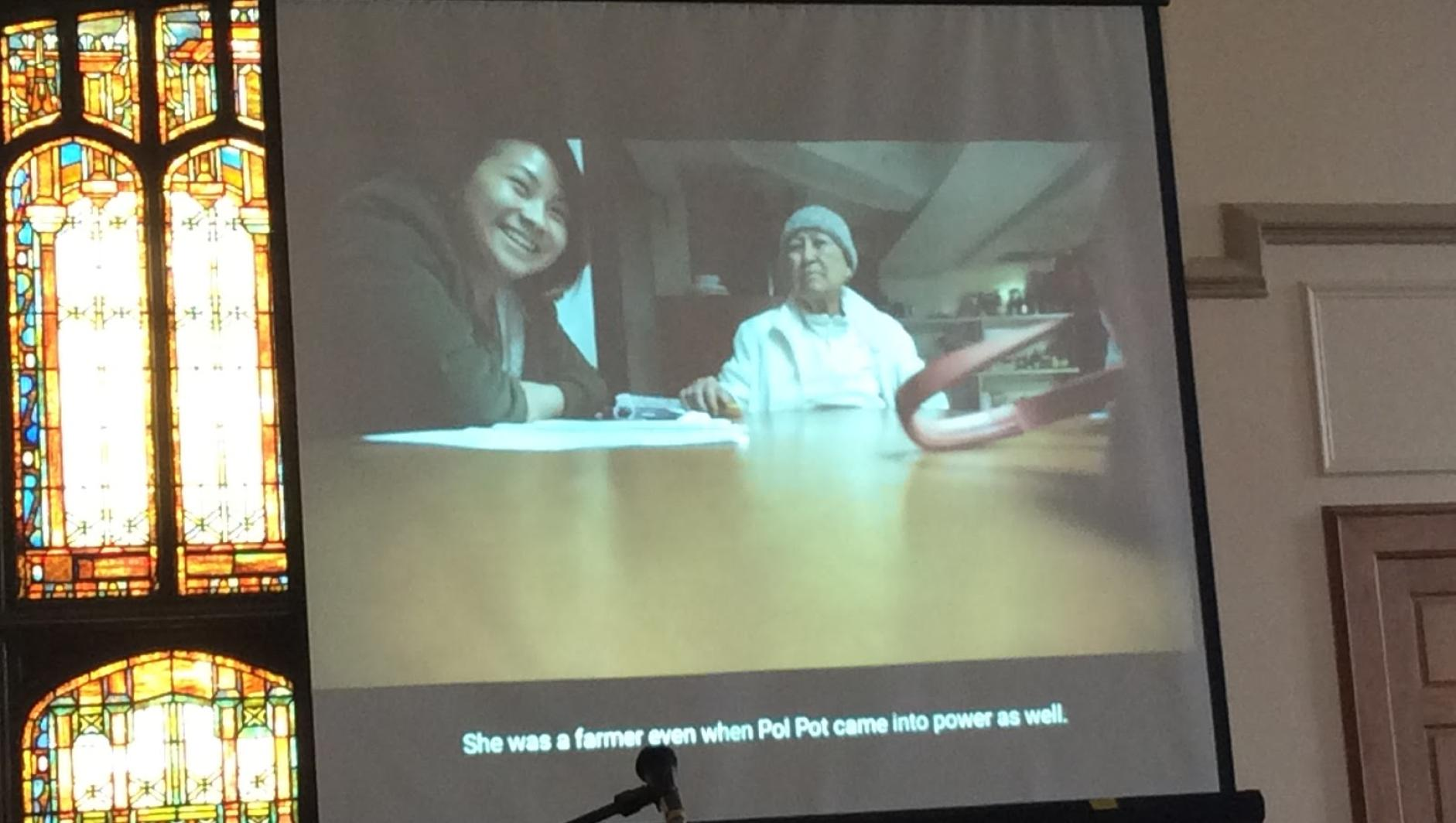 Projector screen shows a Springfield College student talking with a relative about Pol Pot