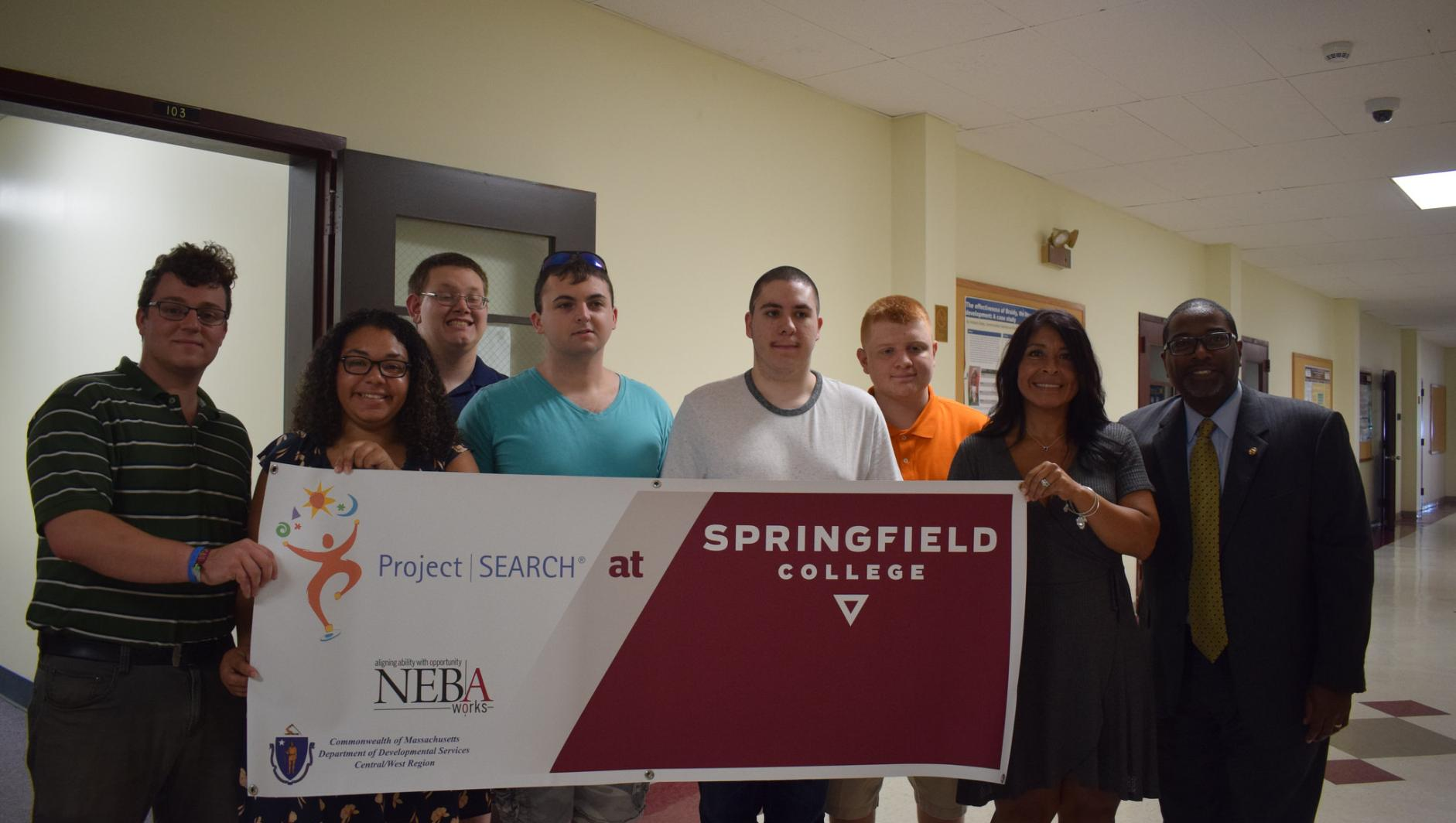 Project Search participants and staff stand with the banner.