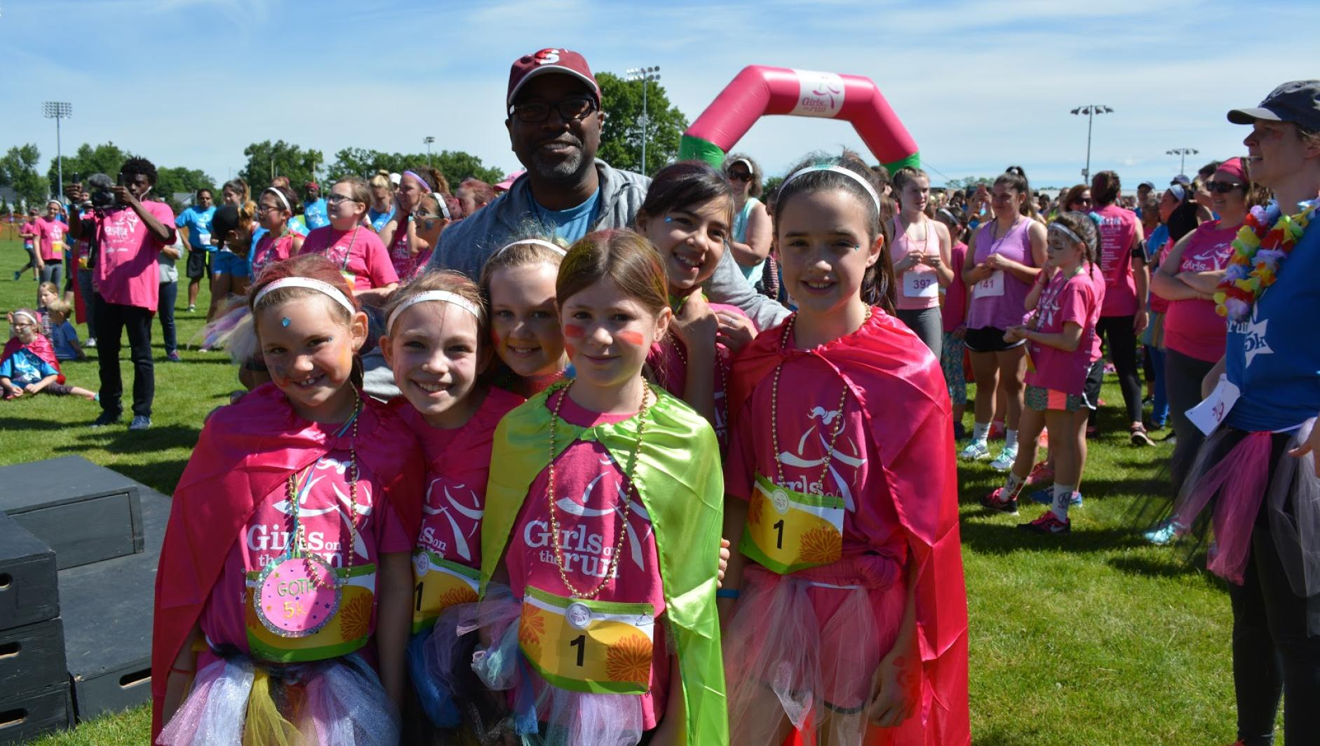 Calvin Hill poses with Girls on the Run participants.