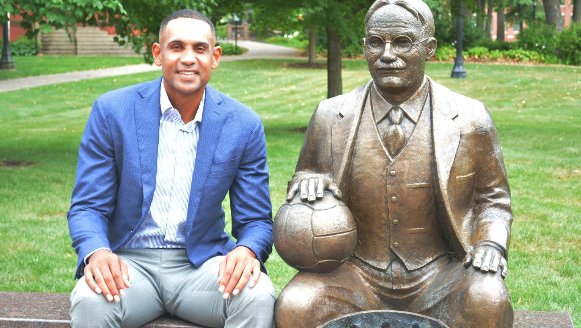 Grant Hill sitting next to the Naismith Statue