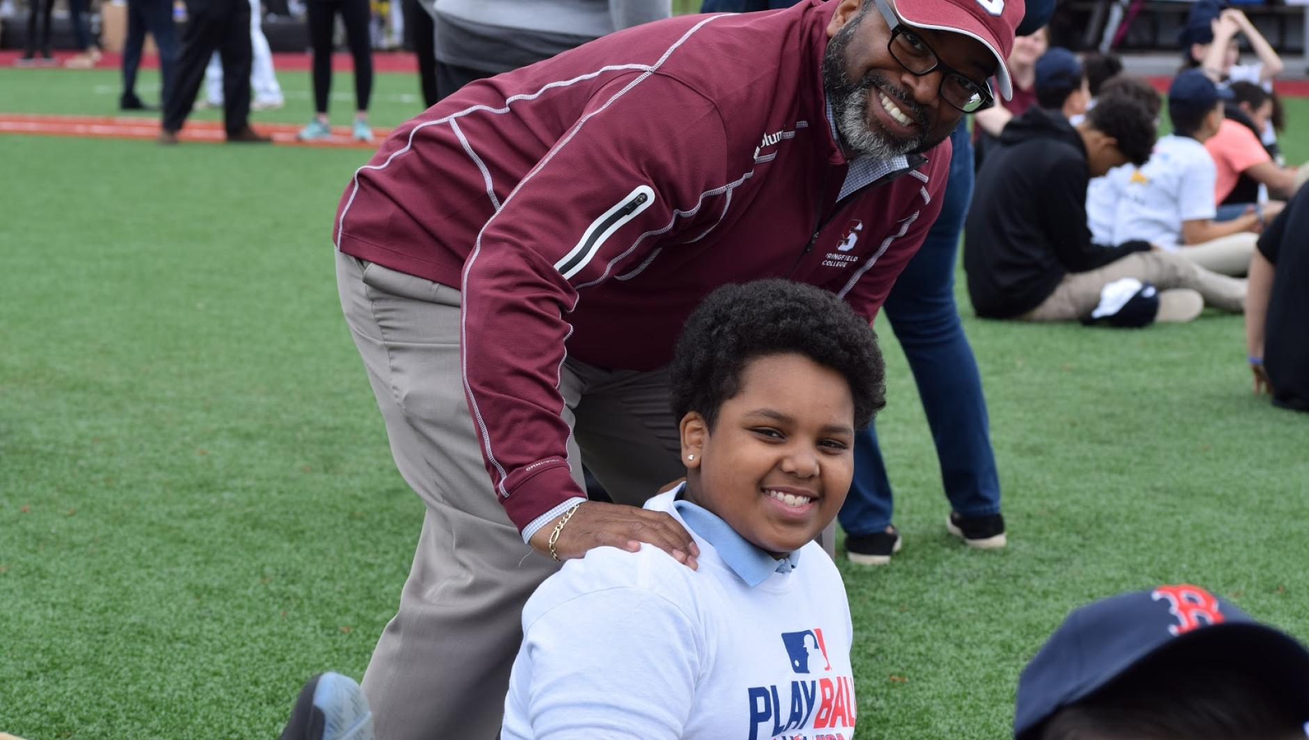 Calvin Hill poses with a participant during Play Ball event.