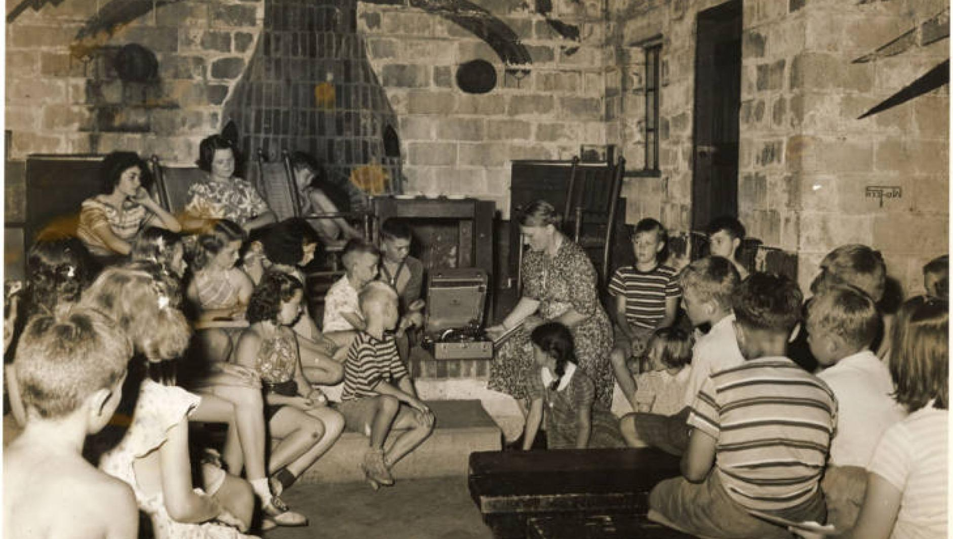 Students sit in a building at Camp Massasoit and listen to music.