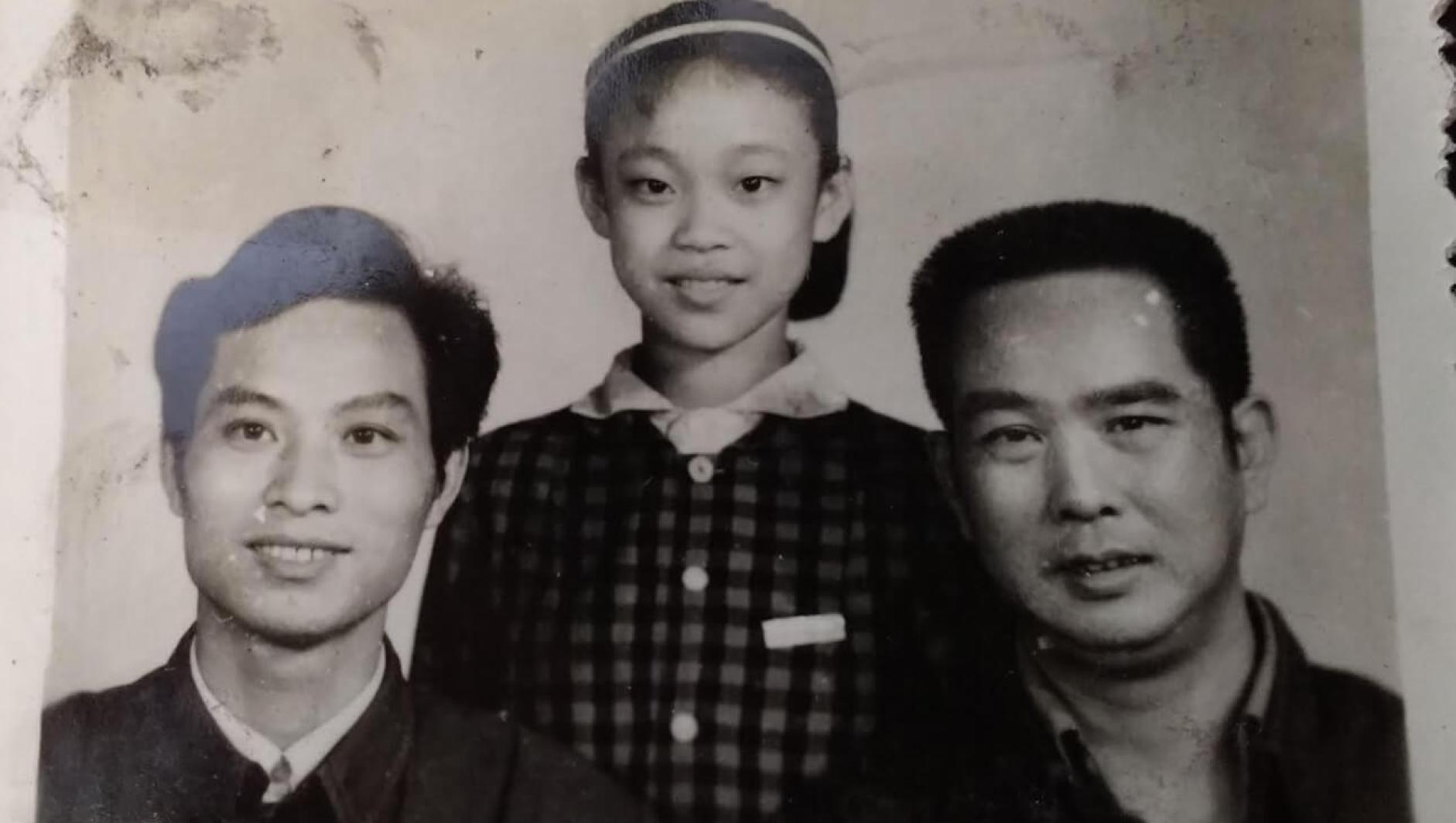 Li Jin as a child stand between her father and uncle.