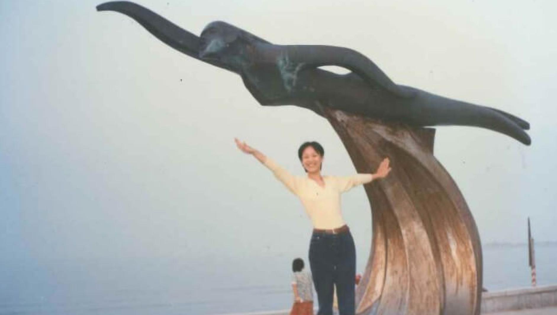 Li Jin poses on a statue of a wave.