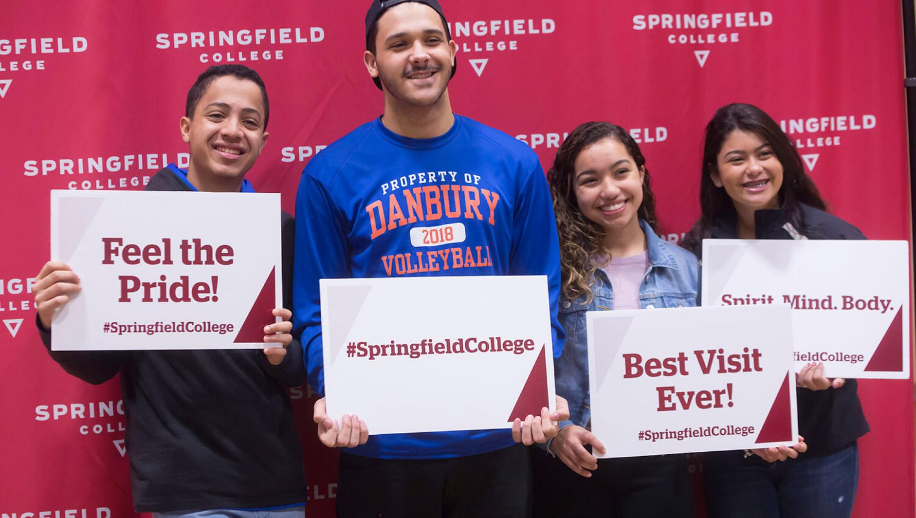 "Students and their family hold photobooth signs saying ""Feel the Pride,"" ""Best Visit Ever!"" and #Springfield College at Springfield College Accepted Students Open House Event"