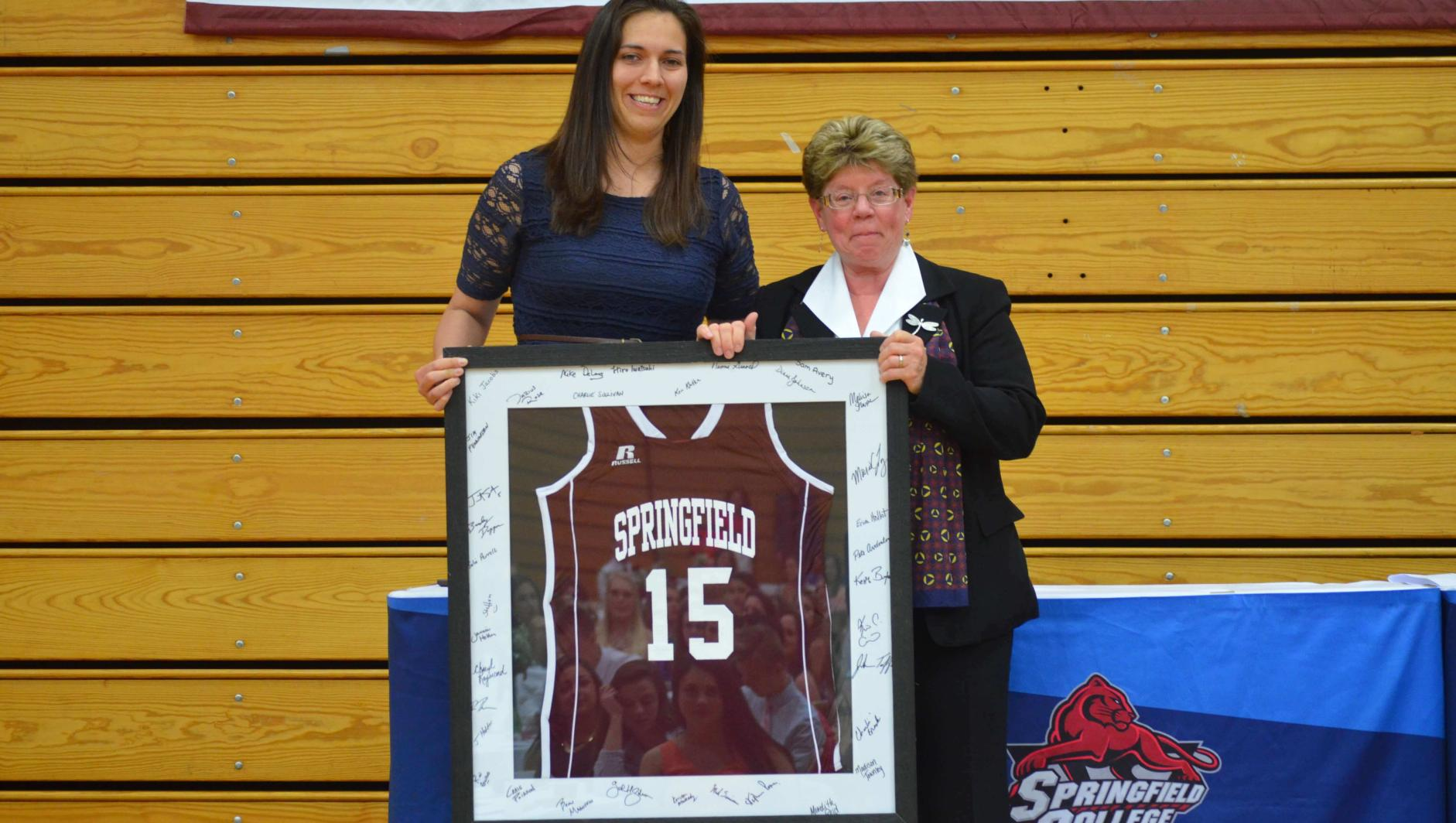 Samantha Avery presents a jersey to a coach.