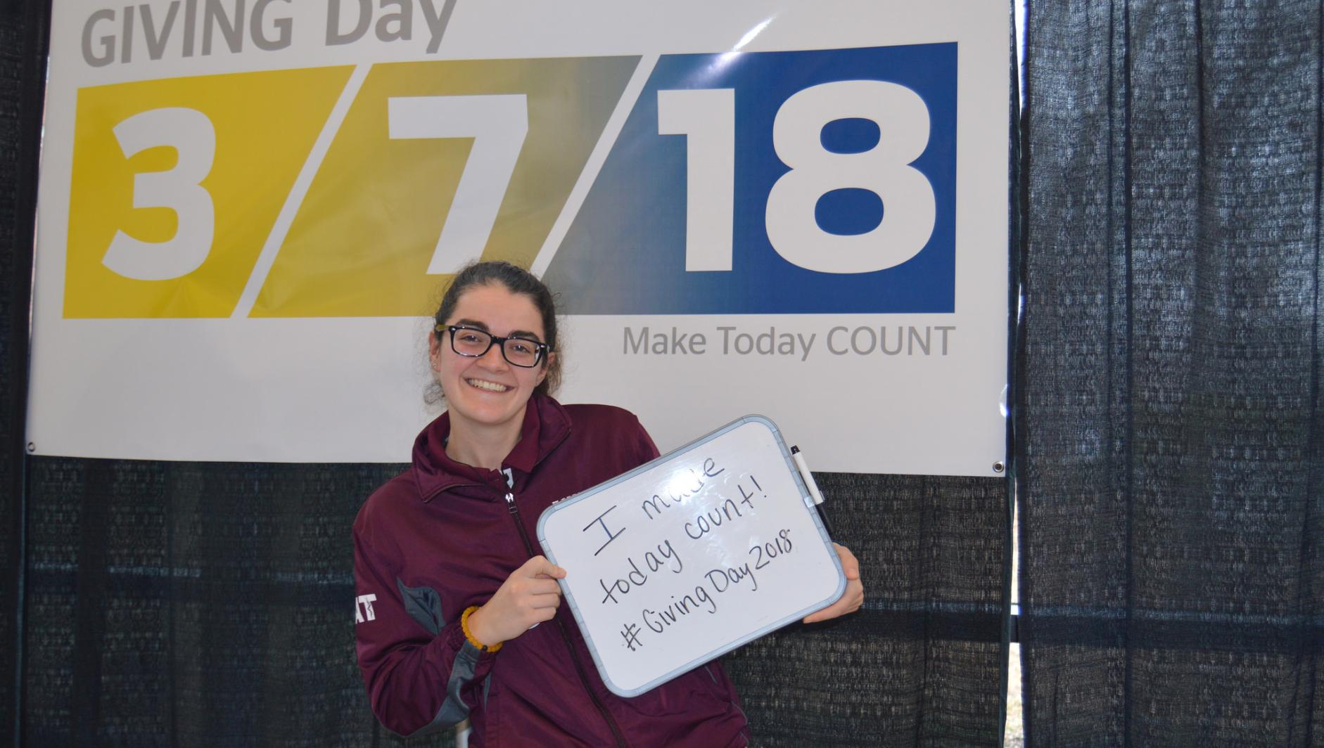 A student holds up a Giving Day sign.
