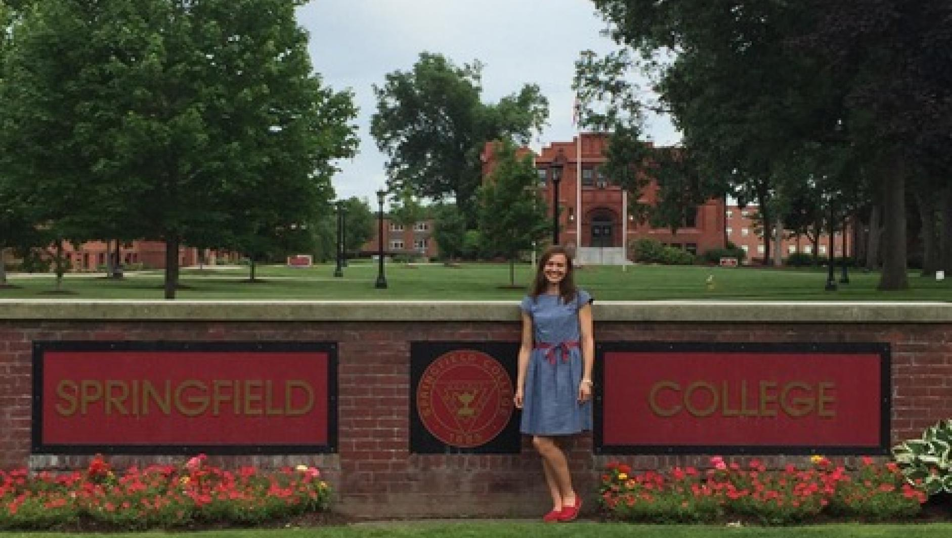 Watkins in front of the Springfield College sign.