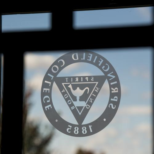 The Springfield College seal is on the window of the door on campus