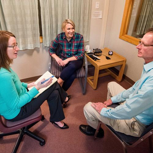 Three individuals sit in a room in a counseling session
