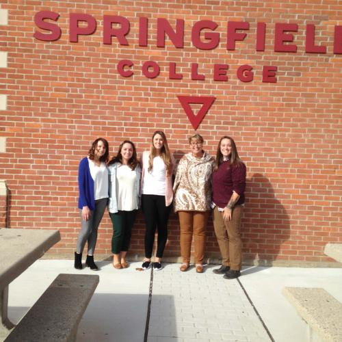 Springfield College Alumni stand under the Springfield College sign on a building