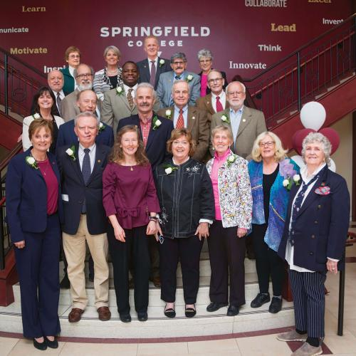 Distinguished Professors of Humanics stand on stairs with President Mary-Beth Cooper