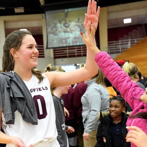 A local school child high fives a member of the Springfield College women's basketball team