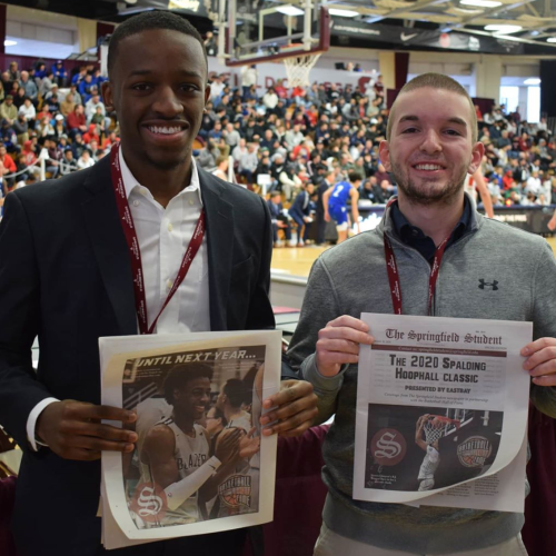 Two COSJ students hold up special copies of the Student Newspaper