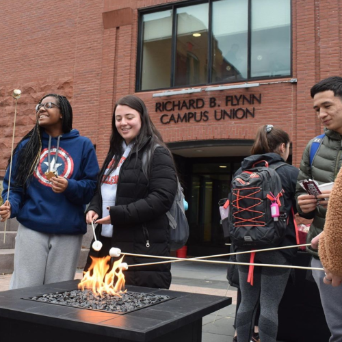 Students roast marshmallows outside the Union during the 10th anniversary celebration.