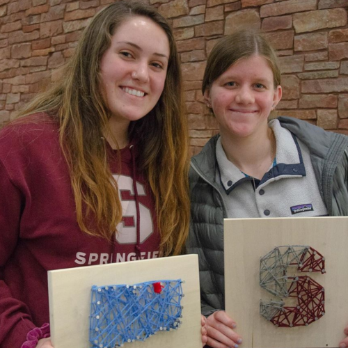 Students pose with their nail and yarn art at the Union