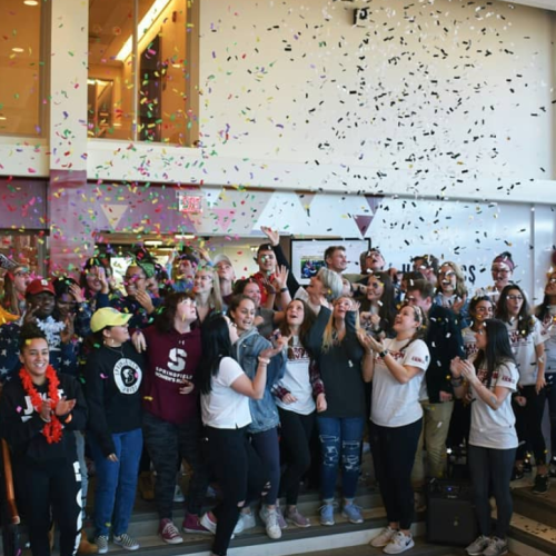 Confetti and a large group in the Union celebrating Giving Day