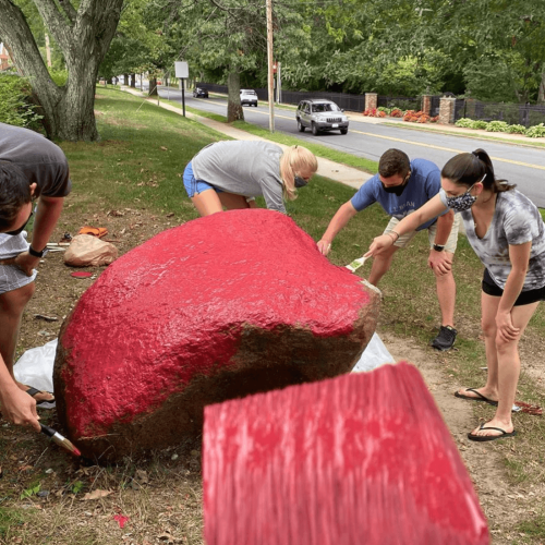 Students painting a large rock