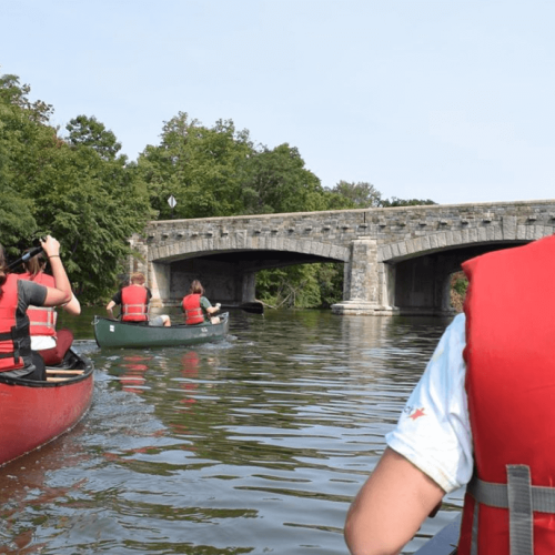 A group of canoes go under a bridge on Lake Massasoit