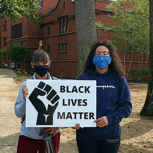 Two young women hold a Black Lives Matter sign