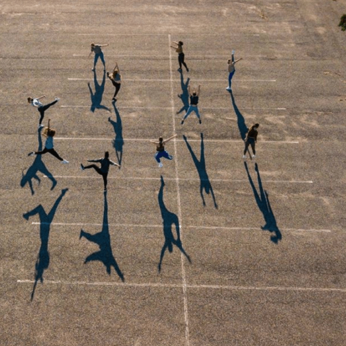 An aerial view of dancers in the parking lot and their shadows